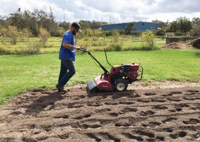 Picture of staff tilling a field