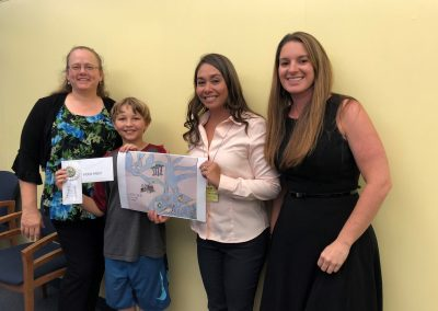 This is a picture of the OSWCD poster contest winner. Aiden Pabst is holding his poster and his award. He is pictured with his teacher and Audrey Kuipers.