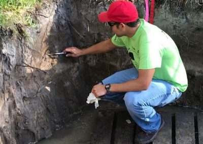 Felix Colon NRCS Civil Engineer shapes the face of a soil profile at the Soil Station