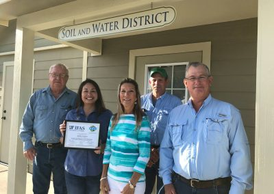 Supervisor Rutledge, Program Manager-Audrey Kuipers, and Supervisors Smith, Sellers and Burnham are pictured outside of the OSWCD building. Audrey is holding an award she received for completing a leadership training.