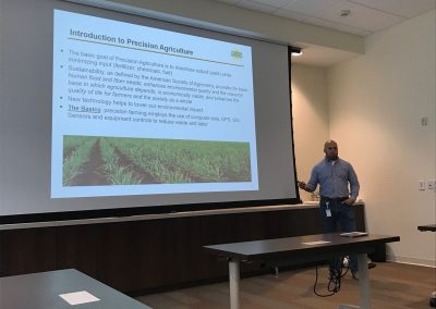 This is a picture of a US Sugar employee giving a presentation on precision agriculture. There is a slideshow presentation behind him on precision agriculture.
