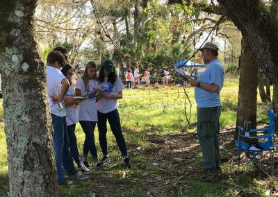 Tim Towles, a FWC Biologist, is pictured administering a question to five students at the Wildlife station. They are outside at the Indian River Lagoon Envirothon competition.