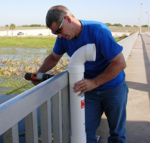 This is a picture of Frank Coker installing a fishing line receptacle on the Jaycee Pier on Lake Okeechobee.